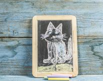 Colorful hand drawing with chalk on blackboard : funny cat. Colorful chalk drawing on blackboard : funny cat hand stock images