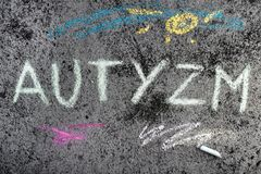 Chalk drawing: Polish word AUTISM and pieces of chalk stock photos