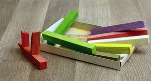 Colorful chalk on the floor. Colored chalk in a cardboard box on the floor Royalty Free Stock Image