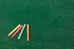 Colorful chalk on green chalkboard royalty free stock photography