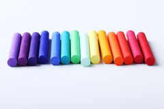 Colorful chalk pastels on white background arranged as rainbow Stock Photography