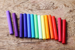 Colorful chalk pastels on wooden background. Arranged as rainbow spectrum Stock Photos