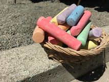 Colorful chalk sticks in the basket to draw art on concrete floor. Outdoor family activities, children learning skills, and talent. S concept royalty free stock photography