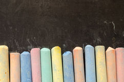 Colorful chalks on blackboard Stock Photo
