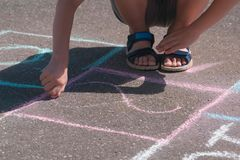 Boy is drawing hopscotch on the asphalt. Close-up hand and legs. Colorful chalks for drawing on asphalt outdoor stock photo
