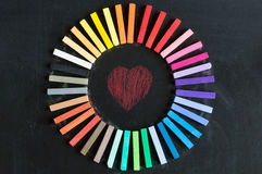 Colorful chalks lined up rounded on circle on blackboard backgro Royalty Free Stock Photography