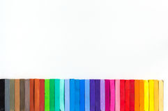 Colorful chalks lined up on white background Royalty Free Stock Photography