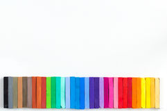 Colorful chalks lined up on white background Stock Photos