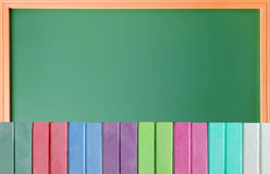 Colorful chalks over school blackboard Royalty Free Stock Photography