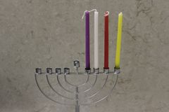 Colorful Chanukah candles lit in the menorah, candle light Stock Photos