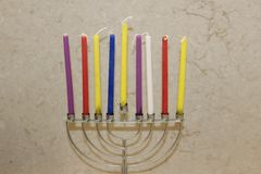 Colorful Chanukah candles lit in the menorah, candle light Stock Photo