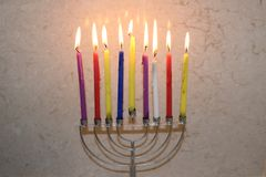 Colorful Chanukah candles lit in the menorah, candle light Royalty Free Stock Photo