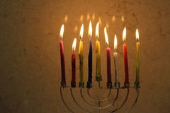 Colorful Chanukah candles lit in the menorah Stock Photo