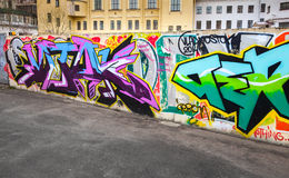 Colorful chaotic graffiti text painted on concrete fence Royalty Free Stock Image