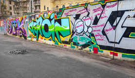 Colorful chaotic graffiti text patterns on concrete fence Stock Photography