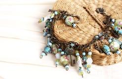 Colorful charm bracelet on cream background. Fashionable colorful charm bracelet lying on woven box lid, shot on cream linen background Stock Images