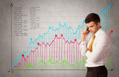 Colorful chart with numbers and businessman. A confident young businessman standing in front of a a chart with graphs and numberswhile talking on the phone Stock Images