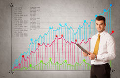 Colorful chart with numbers and businessman. A confident young businessman standing in front of a a chart with graphs and numberswhile talking on the phone Royalty Free Stock Photos