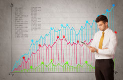 Colorful chart with numbers and businessman. A confident young businessman standing in front of a a chart with graphs and numberswhile talking on the phone Stock Photography