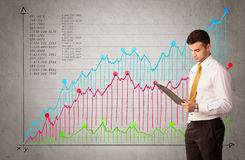 Colorful chart with numbers and businessman. A confident young businessman standing in front of a a chart with graphs and numberswhile talking on the phone Stock Photo