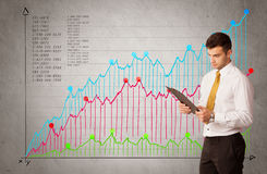 Colorful chart with numbers and businessman. A confident young businessman standing in front of a a chart with graphs and numberswhile talking on the phone Royalty Free Stock Image