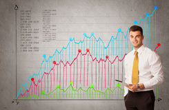 Colorful chart with numbers and businessman. A confident young businessman standing in front of a a chart with graphs and numberswhile talking on the phone Royalty Free Stock Photo