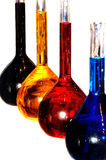Colorful chemistry liquid glass retorts isolated. Alchemy glass retorts with colorful liquid printer paint isolated on white stock images