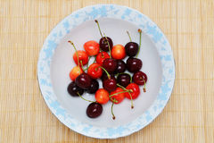 Colorful cherries on plate Stock Photo
