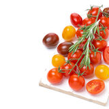 Colorful cherry tomatoes and rosemary on a white wooden board Royalty Free Stock Photography