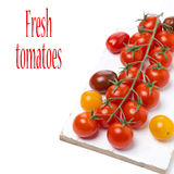 Colorful cherry tomatoes on a white wooden board, isolated Stock Photography