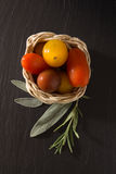 Colorful cherry tomatoes in wicker basket with herbs Royalty Free Stock Photos