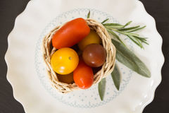 Colorful cherry tomatoes in wicker basket with herbs Royalty Free Stock Image