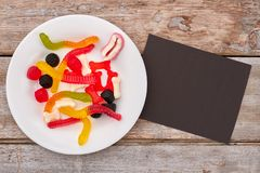 Colorful chewy candies on plate. Assorted jelly candies and black paper card. Junk food concept royalty free stock photography
