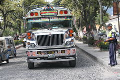 Colorful Chicken Bus in Antigua, Guatemala. A colorful chicken bus is parked in front of an old church on one of Antigua, Guatemala's narrow cobbled streets Royalty Free Stock Photos