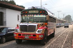 Colorful Chicken Bus in Antigua, Guatemala. A colorful chicken bus is parked in front of an old church on one of Antigua, Guatemala's narrow cobbled streets. Red Royalty Free Stock Photography