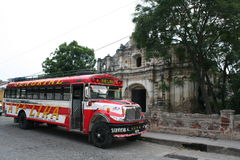 Colorful Chicken Bus on straiten Antigua, Guatemala. A colorful chicken bus is parked in front of an old church on one of Antigua, Guatemala's narrow cobbled Stock Photo