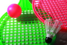 Colorful chidren toy racket with two balls. Green and pink toy rackets and two plastic balls close up  photo with side lighting effect Royalty Free Stock Images