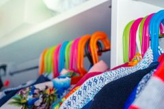 Colorful child hangers with toddler boy shirts hanging in a closet stock images