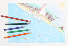 Colorful child's drawing of a ship at sea and crayons Stock Photos