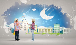 Colorful childhood. Two children of school age painting wall in colors Royalty Free Stock Image