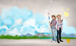 Colorful childhood. Two children of school age painting wall with roller Stock Images