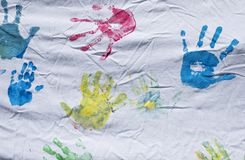 Colorful children hand prints. Diverse colorful children`s hand prints on a white sheet stock photo