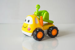 Colorful, children plastic toy, toy truck tractor with a smile a stock photos