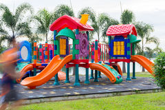 Colorful children playground in the park with a man running move Stock Images