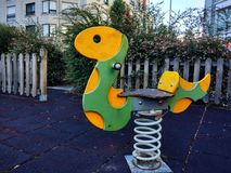 Colorful children playground in public park surrounded by green vegetation with children snake toy close up. Colorful children playground in public park stock photo