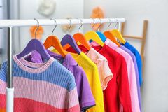 Colorful children`s clothes hanging on wardrobe rack indoors. Closeup stock image