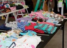 Colorful children`s pajamas a suburban yard sale. Tables of colorful children`s pajamas and clothes for sale at a suburban yard sale Stock Image