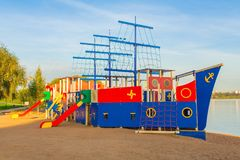 Colorful children`s playground in the form of a ship on the shor. E of the lake Stock Images