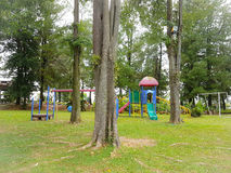 Colorful children's playground with lush trees and grass. Colorful children's playground with trees and grass in sight in a peaceful and serene environment for Stock Photos