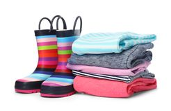 Colorful children`s rubber boots and stack of clothes. On white background stock images